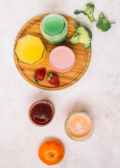 Flat lay colorful arrangement of smoothies and fruits
