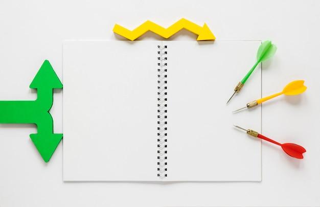 フラット横たわっていたカラフルな矢印とノートブックのモックアップ