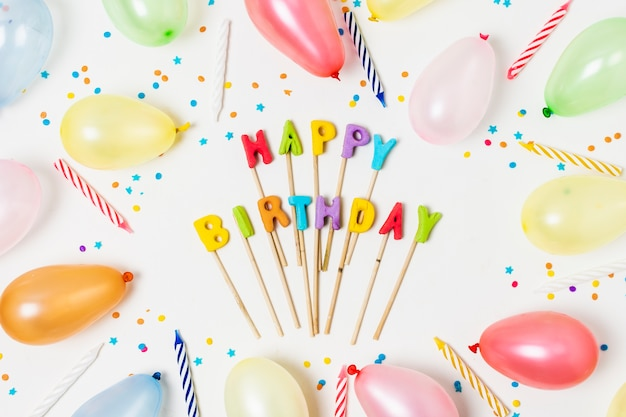 Flat lay colorful balloons on white background with birthday lettering