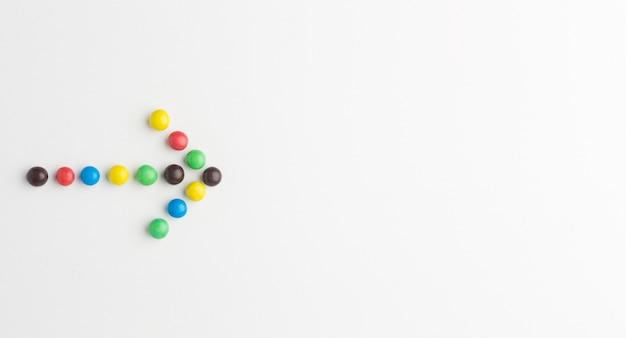 Flat lay of colorful candy arrow with copy space