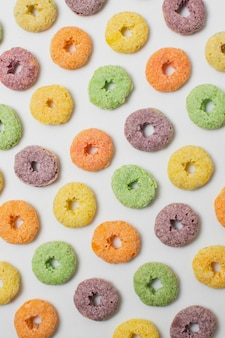 Flat lay colorful circular cereals on white background
