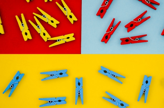 Flat-lay colorful clothes pins on colored backgrounds