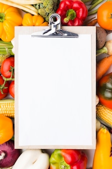 Flat lay colorful composition of vegetables with clipboard