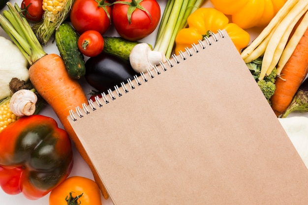 Flat lay colorful composition of vegetables with notepad