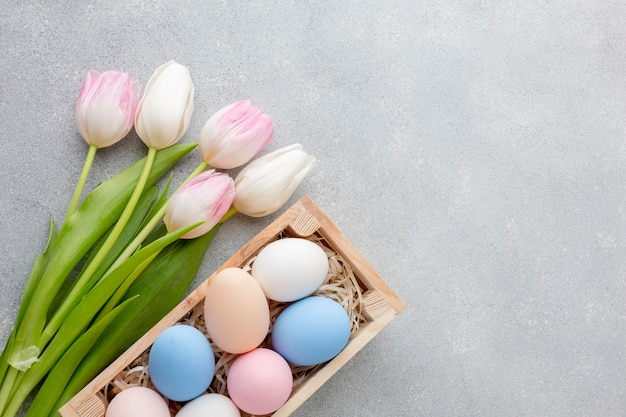 Flat lay of colorful easter eggs in box with tulips and copy space