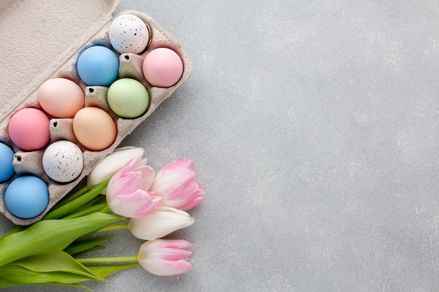 Flat lay of colorful easter eggs in carton with tulips and copy space