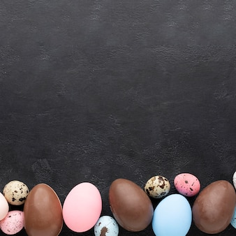 Flat lay of colorful easter eggs and chocolate ones