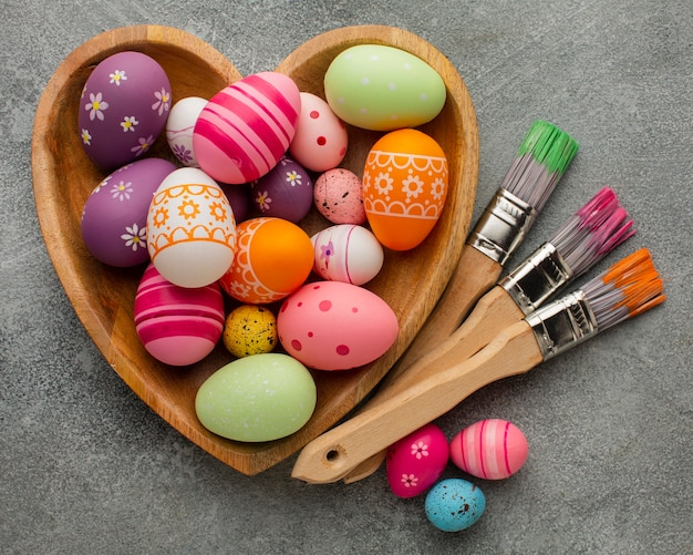 Flat lay of colorful easter eggs in heart shaped plate with paint brushes