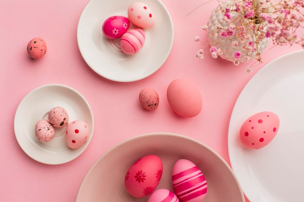 Flat lay of colorful easter eggs on plates with paper and flowers