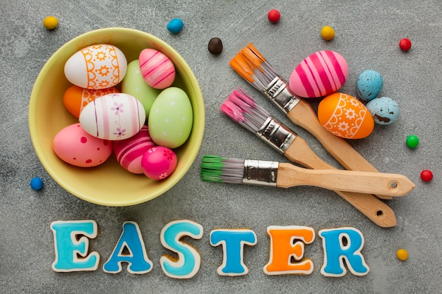 Flat lay of colorful easter eggs with paint brushes