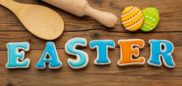 Lay piatto di uova di pasqua colorate con mattarello e cucchiaio di legno