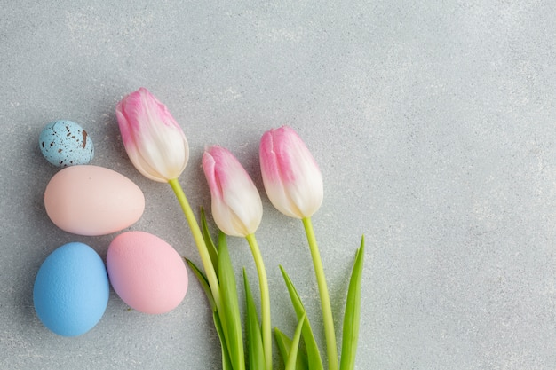 Flat lay of colorful easter eggs with tulips