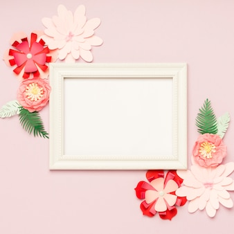 Flat lay of colorful paper flowers and frame