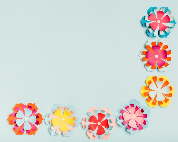 Flat lay of colorful paper flowers for spring with copy space