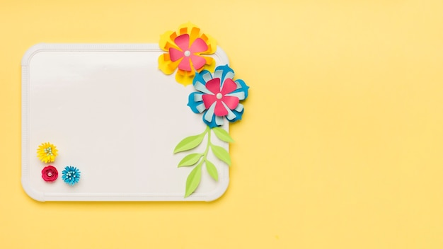 Flat lay of colorful paper flowers on whiteboard