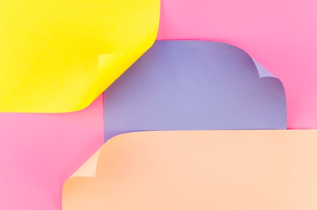 Flat lay of colorful paper sheets with bent corners