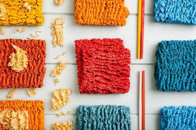Tagliatelle ramen colorate distese piatte e bacchette colorate