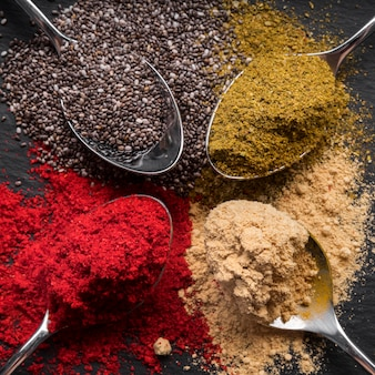 Flat lay colorful spices on black background