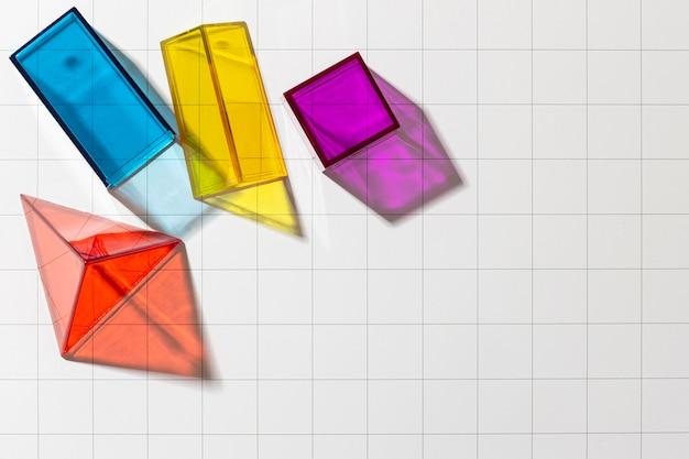 Disposizione piatta di forme geometriche traslucide colorate con spazio di copia