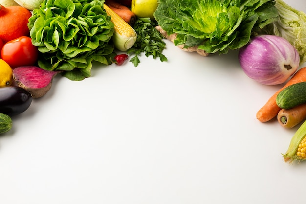 Flat lay colorful veggies on white background with copy space