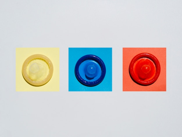 Flat lay coloured condoms on white background