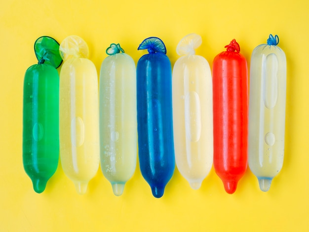Flat lay colourful condoms filled with water