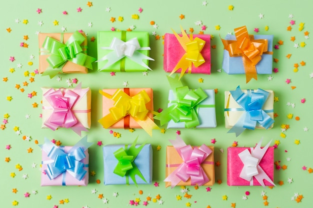 Flat lay colourful gifts on table with green background