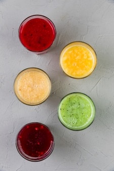 Flat lay colourful smoothie glasses