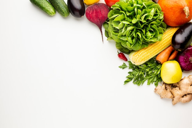 Flat lay colourful veggies on white background with copy space