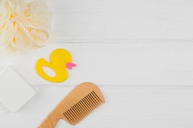 Flat lay of comb with ducky and loofah for baby shower