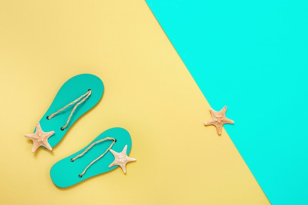 Flat lay of composed miniature of beach lounge area with summer shoes - flip-flops and small sea stars on bright paper.  minimal style. copy space.