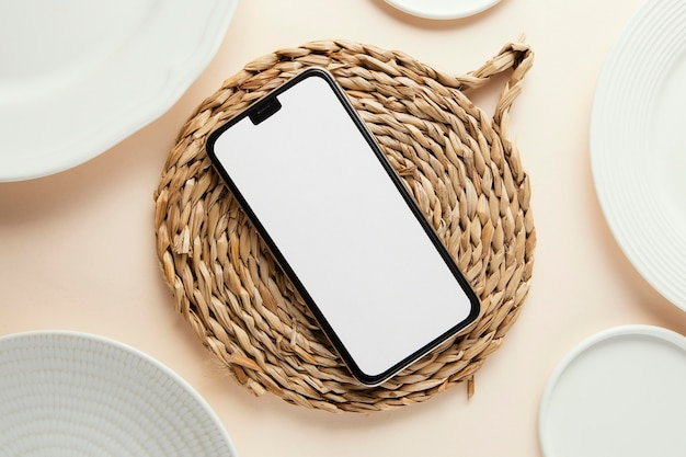 Flat lay composition of beautiful tableware with empty smartphone