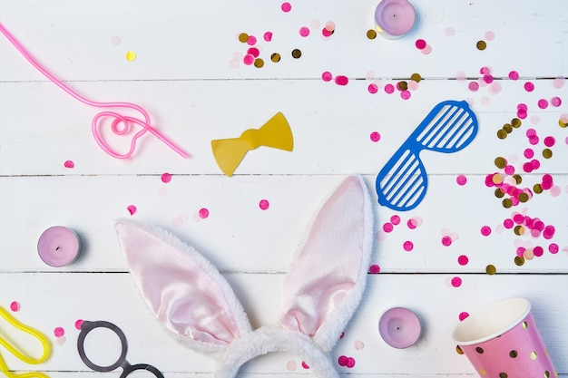 Flat lay composition of birthday party background with confetti, glass, masks, hare ears