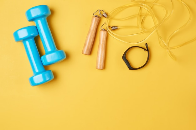 Flat lay composition of blue dumbbells, jump rope and fitness tracker on a yellow background with copy space