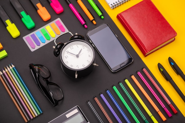 Flat lay composition of business desk with alarm clock, smartphone, notebook, stickers, and colored pens