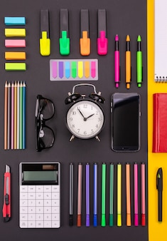 Flat lay composition of business desk with smartphone, calculator, stickers, and pens on colorful black and yellow background