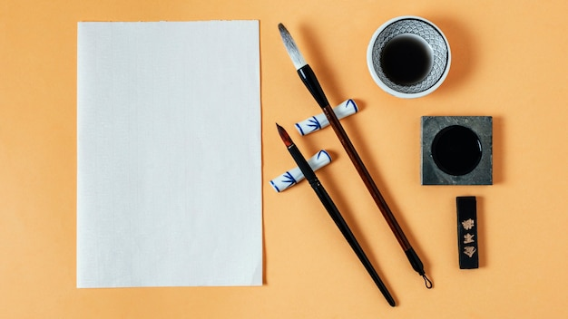 Flat lay composition of chinese ink with empty paper