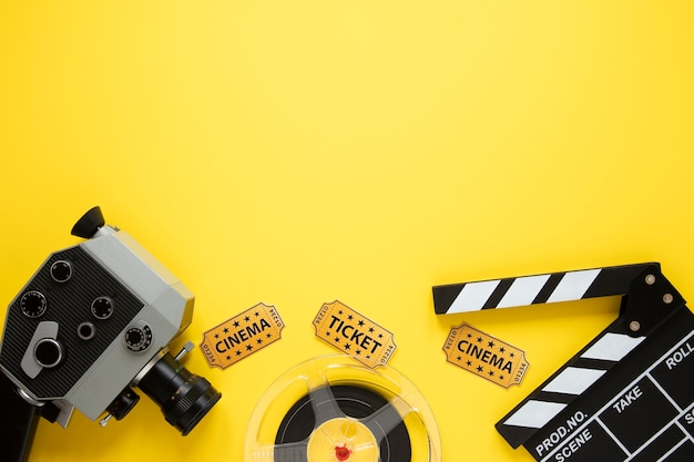 Flat lay composition of cinema elements on yellow background with copy space