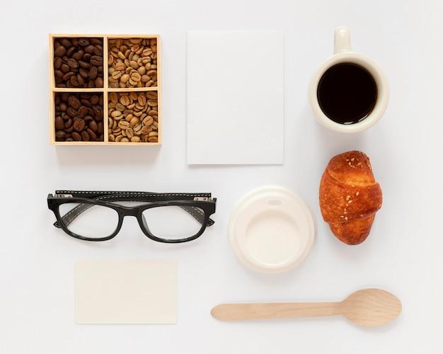 Composizione piatta laici di elementi di branding di caffè su sfondo bianco