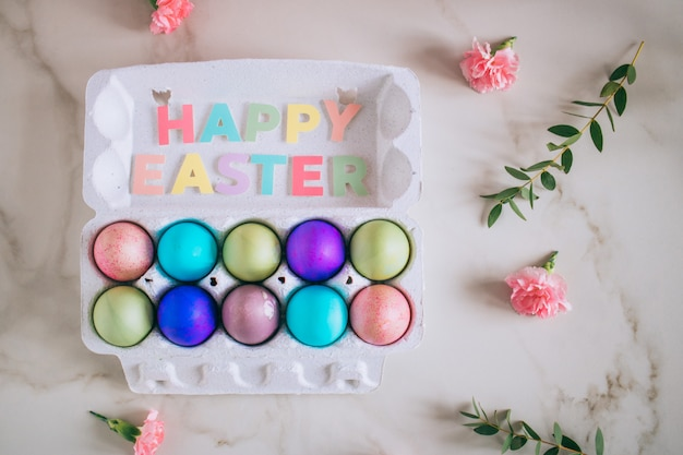 Flat lay composition of colored easter eggs lying in tray on marble table background