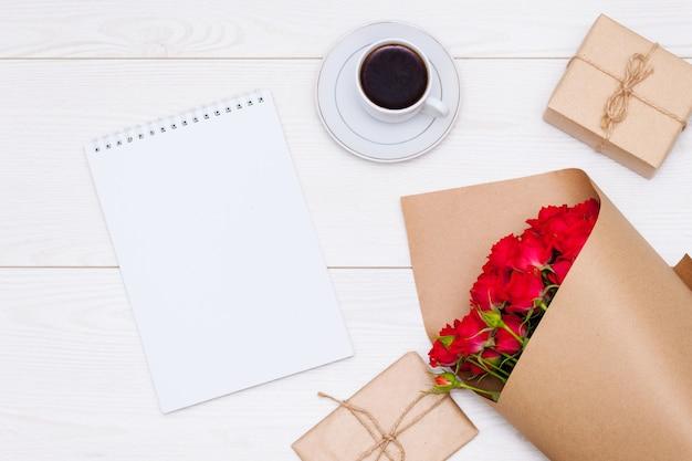 フラットレイ構成。一杯のコーヒー、赤いバラ、ギフトボックス、ノート。天然素材のコンセプト。