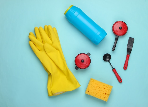Flat lay composition of dishwashing products, toy kitchen tools and utensils on blue.
