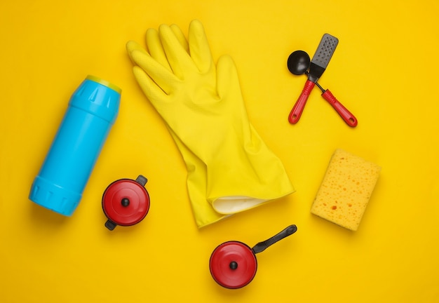 Flat lay composition of dishwashing products, toy kitchen tools and utensils on a yellow.