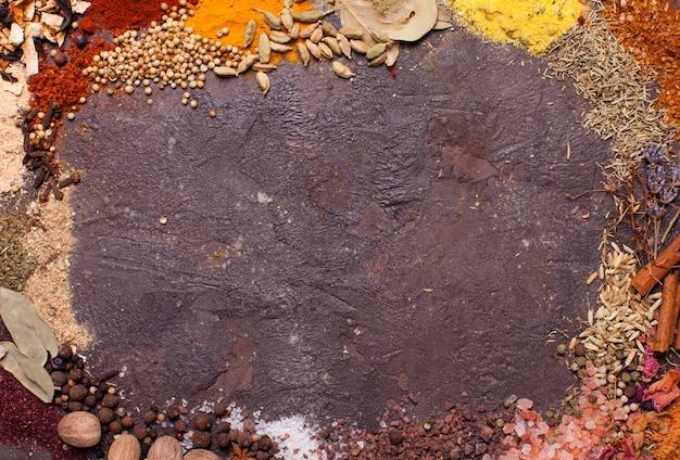 茶色のスレートの背景、上面図上のさまざまなスパイスのフラットレイ構成フレーム