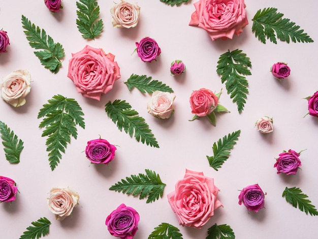 Flat lay composition of green fern leaves and roses of varying size