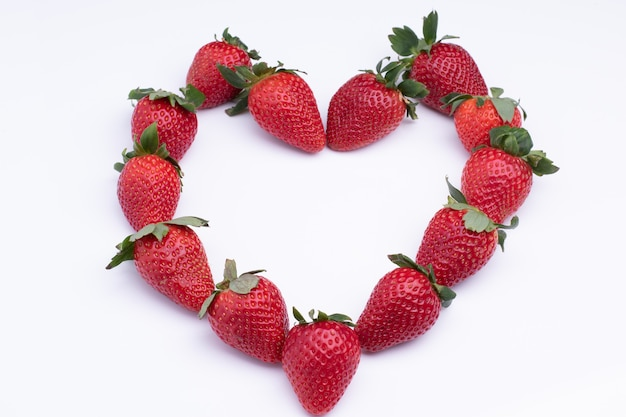 Flat lay composition in heart shape with fresh strawberry isolated on white surface, pattern of berries.