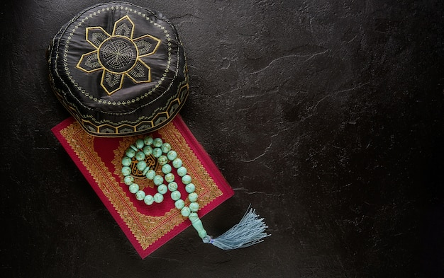 Flat lay composition of holy book for muslim quran, rosary beads and pray hat