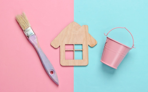 Flat lay composition. house figurine, mini bucket and paint brush on blue pink. pastel color trend.