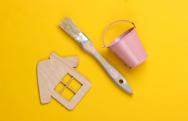 Flat lay composition. house figurine, mini bucket and paint brush on yellow. pastel color trend.