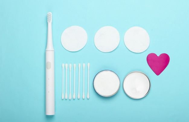 Flat lay composition of hygiene products. toothbrush, cotton pads, ear sticks, cream on a blue background. top view